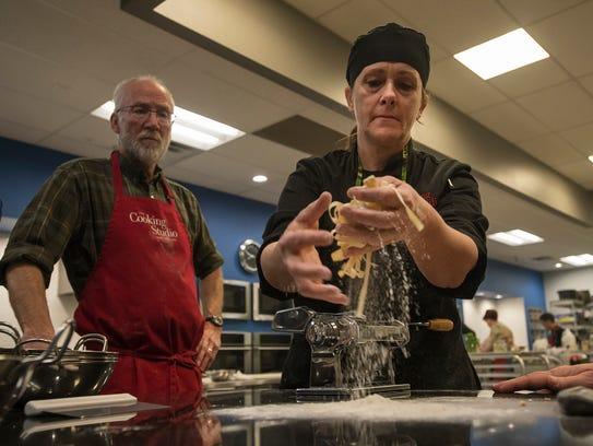 Chef instructor Liz Barnez shows Dan Meyer how to toss