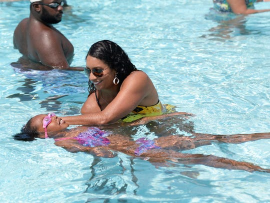 Olympian Maritza McClendon, teach Amyra Spears,9, of Detroit how to float and kick on her back during a swim lesson at Chandler Park during the swim clinic.