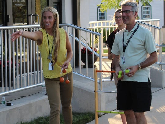 Ginna Petrillo (left) plays the game Ladder Ball with co-workers Joseph Soprani (right) and Sara Kosch (behind) outside of Kramer Hall.