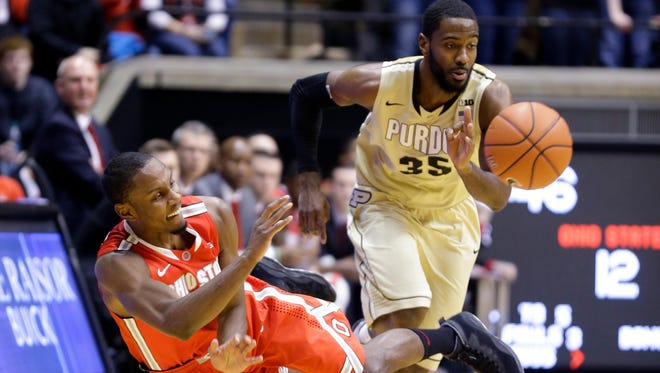 Ohio State forward Sam Thompson (12), left, makes a pass after a diving steal in front of Purdue guard Rapheal Davis (35) in the first half of an NCAA college basketball game in West Lafayette, Ind., Wednesday, Feb. 4, 2015.  (AP Photo/Michael Conroy)