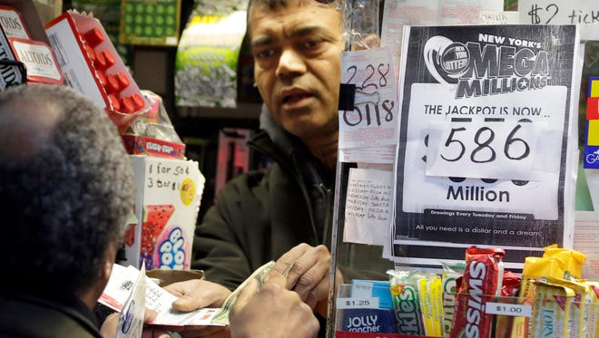 A man buys a Mega Millions lottery ticket at a corner newsstand in New York on Dec. 17.