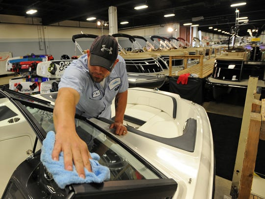 Adam Smith shines the windshield of a boat in the Sea Ray of Greenville booth while setting up for the 46th Annual Upstate SC Boat Show at the TD Convention Center on Wednesday, January 27, 2016.