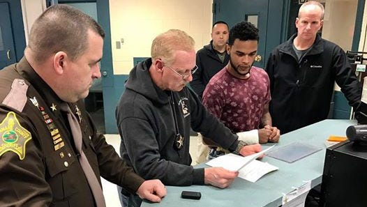 Sheriff Ray Dudley look on as Capt. George Sheridan processes James T. Cole - facing robbery and attempted murder charges - at the Delaware County jail on Friday afternoon.
