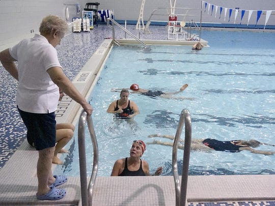 Coach Joyce Lindeman talks with swimmers before practice.
