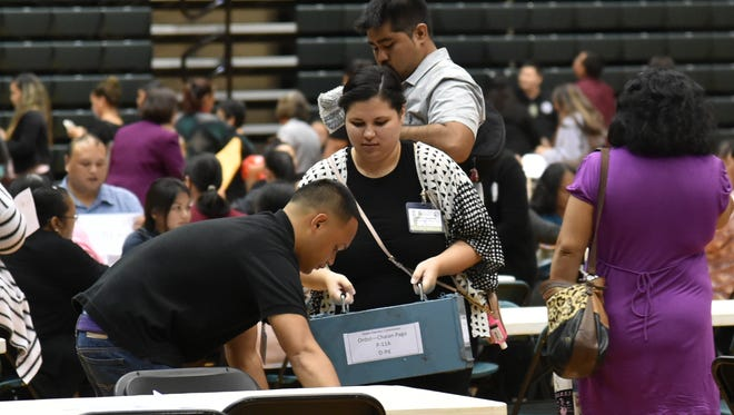 Precinct officials reconcile ballots on the night of the general election at the University of Guam Calvo Field House on Nov. 8, 2016.