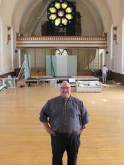 "Jim Stump, producing artistic director of New Edgecliff Theatre, standing in the company's new home in the former St. Patrick's Catholic Church on Blue Rock Street in Northside. The former church complex is home to Urban Artifact Brewing. Behind Stump is what will become the set of the company's first production in the space, Terrence McNally's ""Frankie and Johnny in the Clair de Lune."""