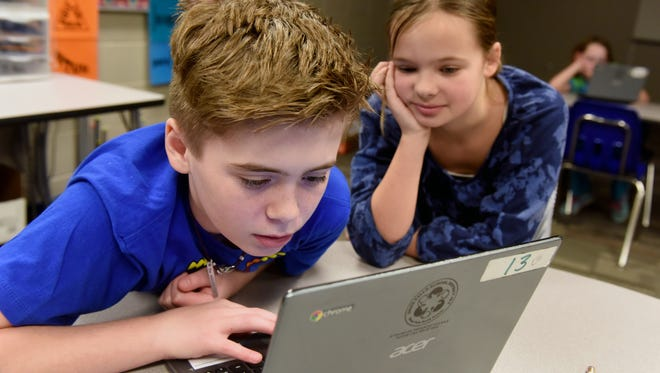 Rocky McKenzie codes while classmate Elizabeth Jensen looks on during Christine Griebel's gifted education class at Sonia Sotomayor Elementary School on Jan. 5, 2017.