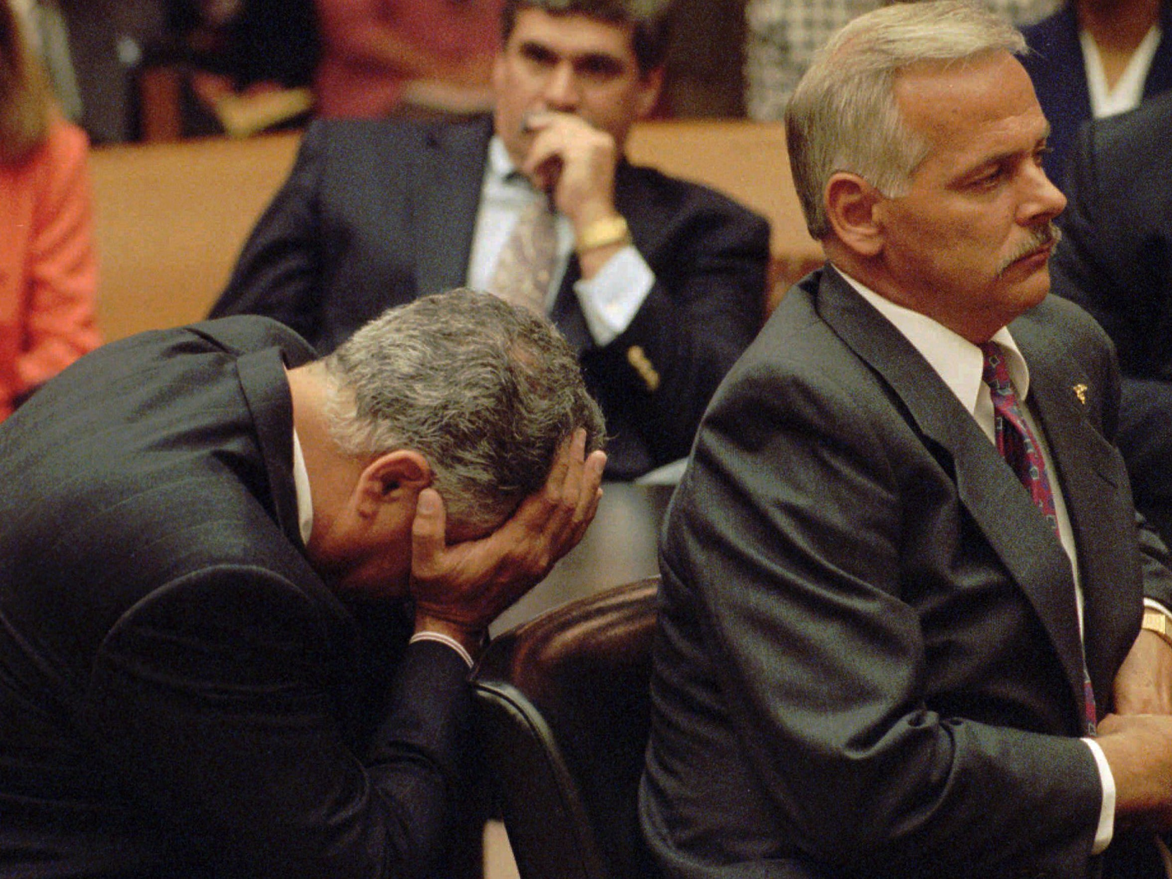 Former Detroit Police officer Larry Nevers, left, holds his face in his hands after hearing Detroit juries found him and his former partner Walter Budzyn, right, guilty of second-degree murder in 1993, in connection with the beating death of Malice Green in Detroit. The charges were later was overturned on appeal, they were re-tried seperatly and found guilty of involuntary manslaughter.