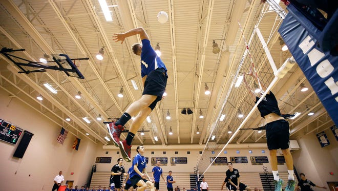 Corvin Walker of Sandra Day O'Connor High jumps high and spikes the ball against  John Tamscin of Mountain Ridge High during boys volleyball playoff action on Thursday, May 7, 2015 at Sandra Day O'Connor High School in Phoenix.