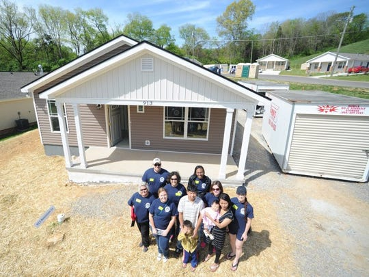Volunteers pose for a photo with the Lazura family outside their nearly-finished home on Anniversary Lane on Friday, April 15, 2016. Habitat for Humanity volunteers from the Knoxville News Sentinel and WBIR-TV worked to help build the house for Sa Lazura, his wife Cherry, and their two children, who settled in Knoxville four years ago after fleeing an oppressive regime in the country of Myanmar.