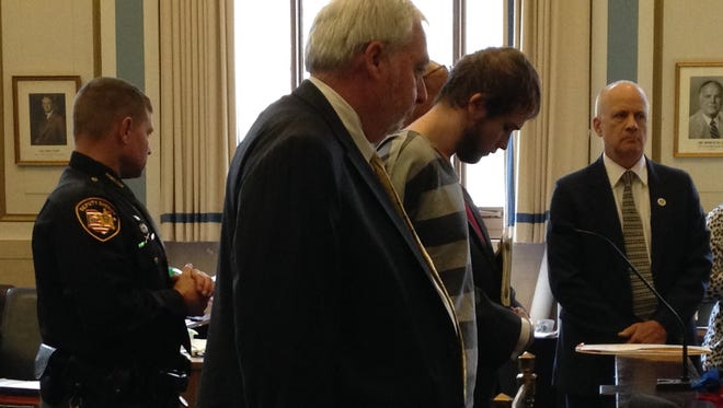 Matthew Hayden, his head bowed, at an arraignment Tuesday in Hamilton County Common Pleas Court. One of his attorneys, Norm Aubin is standing to his right.