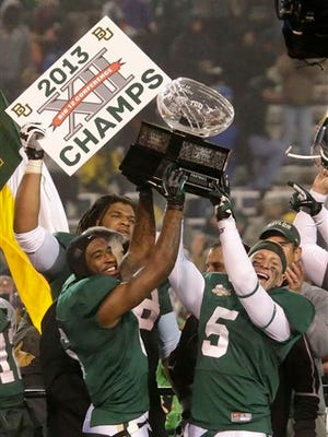 Baylor safety Ahmad Dixon (left) and linebacker Eddie Lackey (5) lift the Big 12 trophy after defeating Texas 30-10 in the conference championship game in Waco, Texas, in 2013. The NCAA board of directors Thursday approved a proposal that would give the five wealthiest college football conferences the ability to make rules and pass legislation without the approval of the rest of Division I schools.