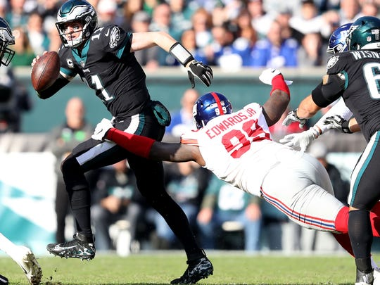 PHILADELPHIA, PENNSYLVANIA - NOVEMBER 25:  Carson Wentz #11 of the Philadelphia Eagles scrambles as Mario Edwards #99 of the New York Giants makes the tackle at Lincoln Financial Field on November 25, 2018 in Philadelphia, Pennsylvania. (Photo by Elsa/Getty Images)