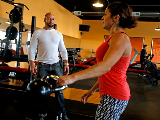 Dean Vaughn, left, owner of Fitness World, spots Stephanie Lobato on Thursday, Oct. 29, 2015 at the gym in Farmington. cq