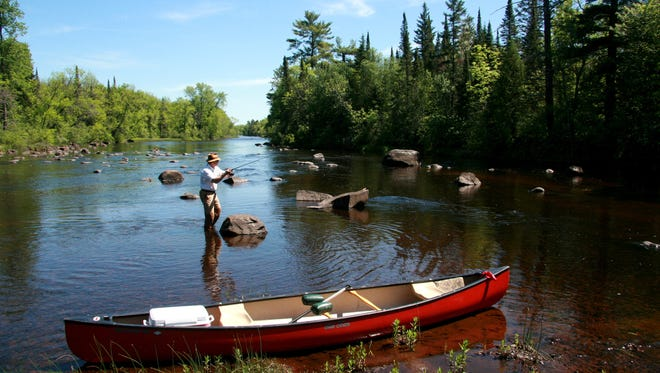 A man fishes and canoes on the St. Croix River in northern Wisconsin, part of the National Wild and Scenic River System preserved with monies from the federal Land and Water Conservation Fund.