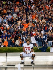 Alabama offensive lineman Chris Owens (79) sits on the bench as Auburn celebrates it's win in the Iron Bowl in Auburn, Ala. on Saturday November 25, 2017. (Mickey Welsh / Montgomery Advertiser)