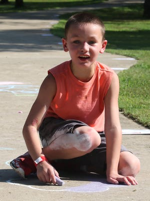 Elijah OKelley shares his vision for his chalk drawings as he creates them on his sidewalk canvas, Saturday, July 11, 2020, during the kid's chalk artist contest in the Barling City Park. Sponsored by the city after having to cancel the Fourth of July event due to COVID-19 concerns, the replacement summer event included frozen treats and drinks and awarded prizes for the best artist in three age groups. Elijah is the 8-year-old son of Alicia and Zachary OKelley.
