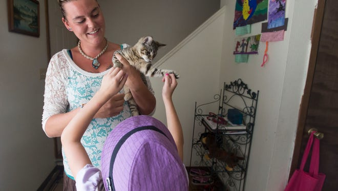 Kyra Smith holds their kitten Squish while her daughter Chloe pets her Friday, July 8, 2016.