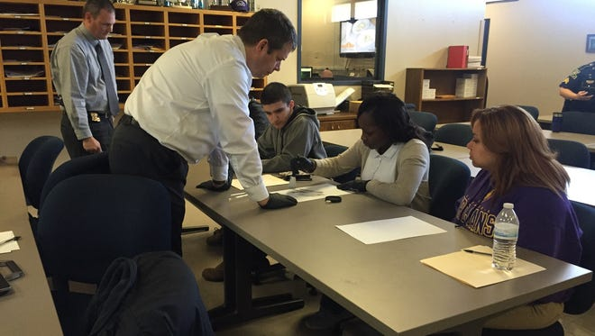 Louisiana State Police Investigator Ronnie Beeson leans over a table while Yasmine Johnson dusts for her own fingerprints. Looking on is fellow Alexandria Senior High student Tyra White (right), Dakota Greer (second from left) and Trooper Rodney Owens (left).