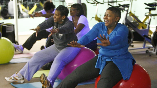 """Sharon Taylor, Rochester, right, reaches out as she joins with others in doing core strengthening exercises during a """"Balls and Bands"""" exercise class at Exercise Express in Rochester on Feb. 27, 2014."""
