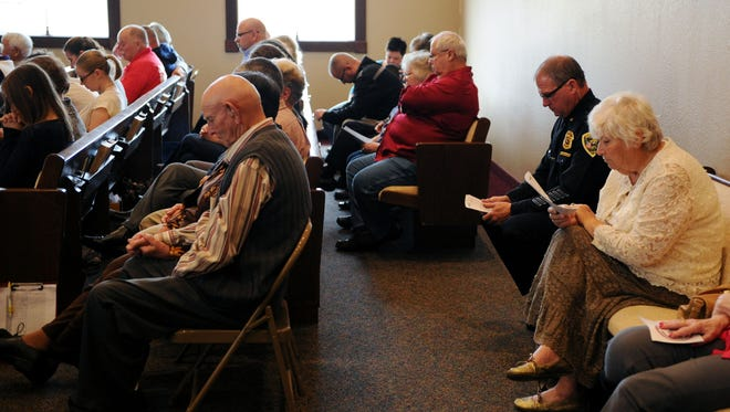 EMILY BROUWER / COURIER & PRESSChurch goers bow their heads in prayer during a service at Baker Chapel on Sunday, Nov. 1, 2015. The service was to honor first responders from the tornado 10 years ago.