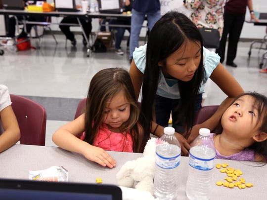 Alice Liu (from left), 6, Harper Norton, 3, Linda Liu, 11, and Vickie Liu, 3, wait while their moms register the older children for school at the Flour Bluff Independent School District on Friday, Sept. 1, 2017. The families are from Port Aransas, TX, an area devastated by Hurricane Harvey. The school district in Port Aransas has declared school indefinitely closed.