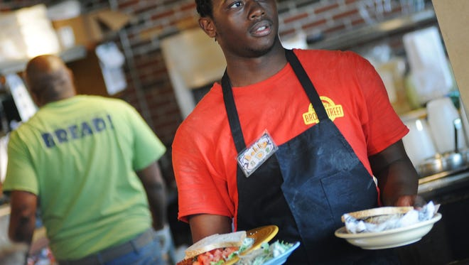 A Broad Street Bakery employee carries plates of food to waiting customers at the Jackson restaurant