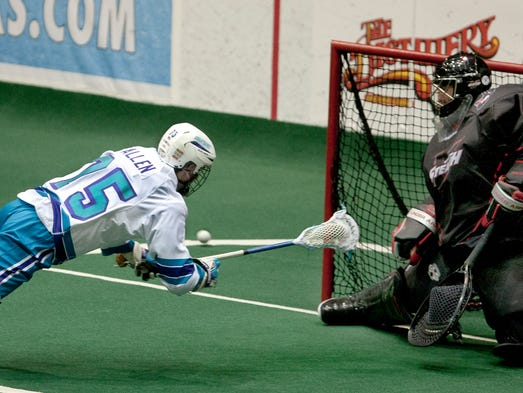 The Knighhawks' Mac Allen dives but misses against Vancouver goalie Matt Roik in the second quarter of their game at Blue Cross Arena on April 12, 2014.