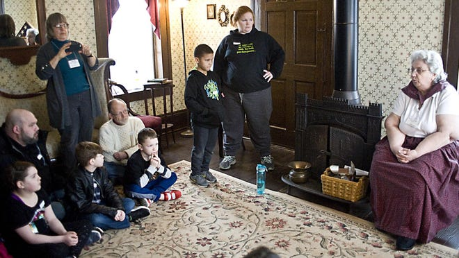 Sylvia George, far right, tells stories about days gone by during an event at Haines House in Alliance. The historic home is part of the new Ohio Literary Trail.