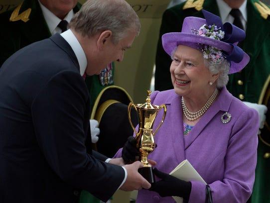 Queen Elizabeth II receives the winning trophy from