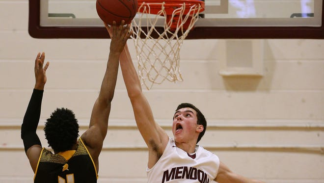 Mendon's Daniel Cook (14) gets the block on this shot by Athena's Kelvin Reaves Jr.