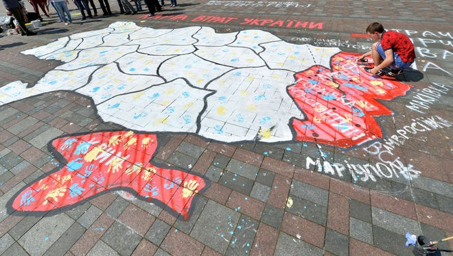 A man paints a symbolic map of Ukraine in Kiev on April 30, with the color red distinguishing the Donetsk region, Lugansk region and Crimea.