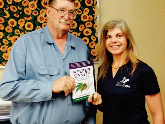 "Woods Houghton, left, co-founder of the Carlsbad Anti-Drug/Gang Coalition, and Eve Flanigan, right, program director, with a copy of ""Reefer Sanity"" by Kevin Sabet. Two copies of Sabet's book were donated to the Carlsbad Public Library."