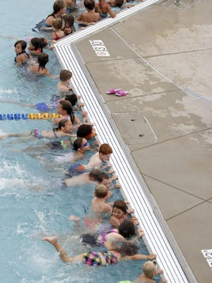 Students kick their feet while hanging onto the wall during the World's Largest Swim Lesson at Altoona Aquatics Park.