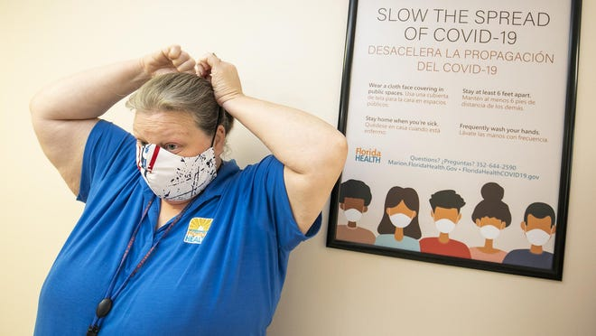 Kelly Conklin puts on her mask as she stands next to a poster reminding people to wear masks to reduce the spread of COVID-19. Conklin, a registered nurse, is the epidemiology and immunization supervisor at the Florida Department of Health in Marion County. She manages the contact tracers who work on contacting people that tested positive for COVID-19. They've been busy thanks to the sharp increase in cases recently.