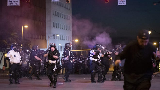 """Columbus Police begin to fire non-lethal """"knee-knocker"""" projectiles to disperse a crowd near the start of curfew in Downtown Columbus on Sunday."""