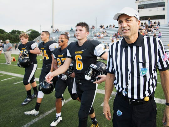 John Mantica, right, leads Bishop Verot High School players to midfield for the coin toss against Estero on Thursday at Bishop Verot in south Fort Myers.