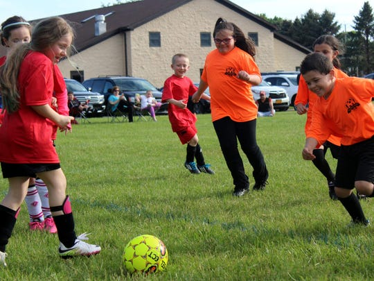 Gabby Howard and her Dynamo teammates are all smiles as they compete in an Irondequoit Soccer Club game held at the Vineyard Church.