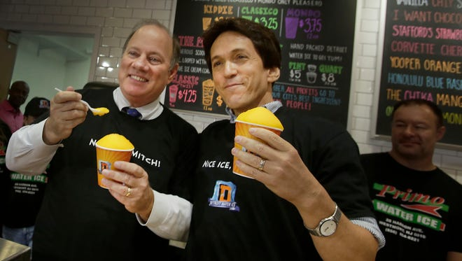 Detroit mayor Mike Duggan and Mitch Albom taste a Chika Mango water ice at the opening of  the Detroit Water Ice Factory on Tuesday, August 4, 2015, in downtown Detroit in the Compuware building.