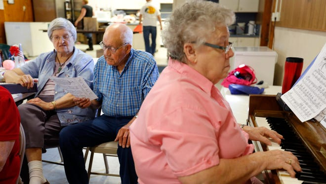 Don Wimmer, 88, and his wife Darlene, 87, sing favorite oldies and hymns as pianist Virginia Walden, 73, of Tingley accompanies at the Tingley Community Center on Aug. 1, 2014.  The center serves as a meal site for the elderly to enjoy some fellowship and lunch together.