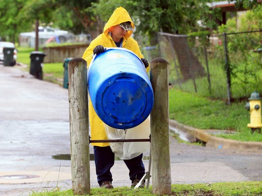 Park technician Ryan O'Daniel from the Corpus Christi Parks & Recreation collects trash as crew members clean up after Easter on Monday, April 17, 2017, at Oak Park in Corpus Christi.
