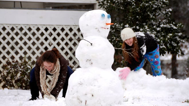 Barrow County residents make a snowman in Euharlee, Ga., about 40 miles north of metro Atlanta, on Tuesday, Feb. 11, 2014.