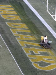 A worker erases the UAB Blazers logo from the end zone