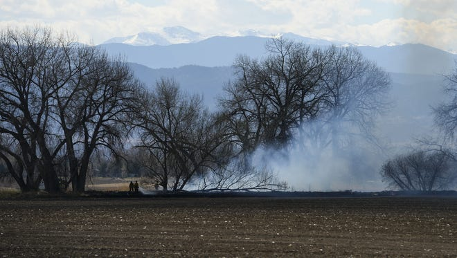 Crews work to control a grassfire near Colorado Highway 14 east of Interstate 25 on March 28, 2015.