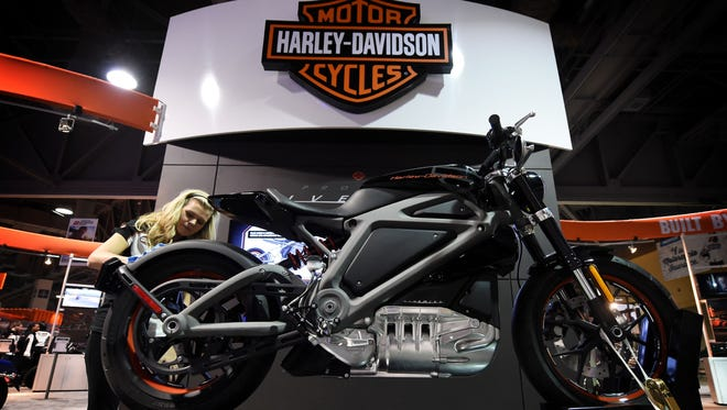 Katie Brierton cleaning the prototype of the Harley-Davidson electric motorcycle called the 'Live Wire' at the Progressive International Motorcycle Show in Long Beach, Calif., in this 2014 file photo
