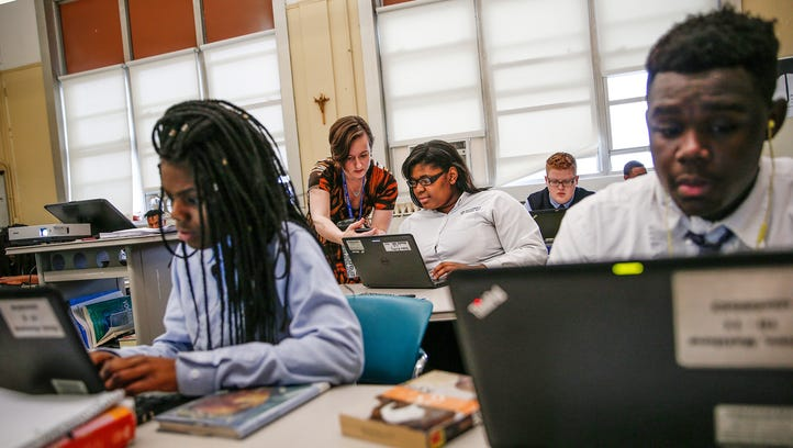 Providence Cristo Rey High School English teacher Frances Klein, middle left, helps student Shanice Beckley with an assignment during class on Monday, Jan. 23, 2017. Providence Cristo Rey High School is a private Catholic high school in Indianapolis that seeks to serve low-income students.