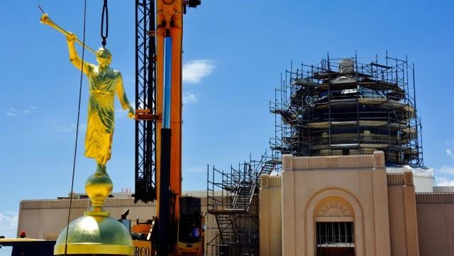 A crane prepares to hoist the Angel Moroni statue to the top of the Tucson temple under construction last July.
