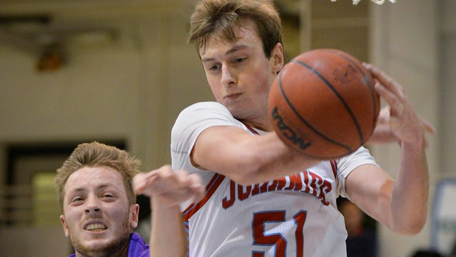 St. Thomas's Grant Shaeffer (4) tries to get a hand on the ball but St. John's post Tyler Weiss (51) comes down with a rebound in the first half Wednesday night, Jan. 13 at Sexton Arena in Collegeville. St. John's was defeated 85-73,