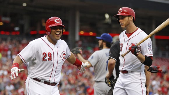 Cincinnati Reds' Brayan Pena, left, celebrates after scoring on a wild pitch with Tony Cingrani, right.