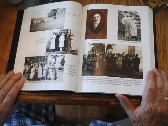 Arnold Dammann's hands frame a book chronicling the 113 year history of the family's farm.  Arnold's grandfather, William Bartels purchased the original 156 acre Page County farmstead in 1901.
